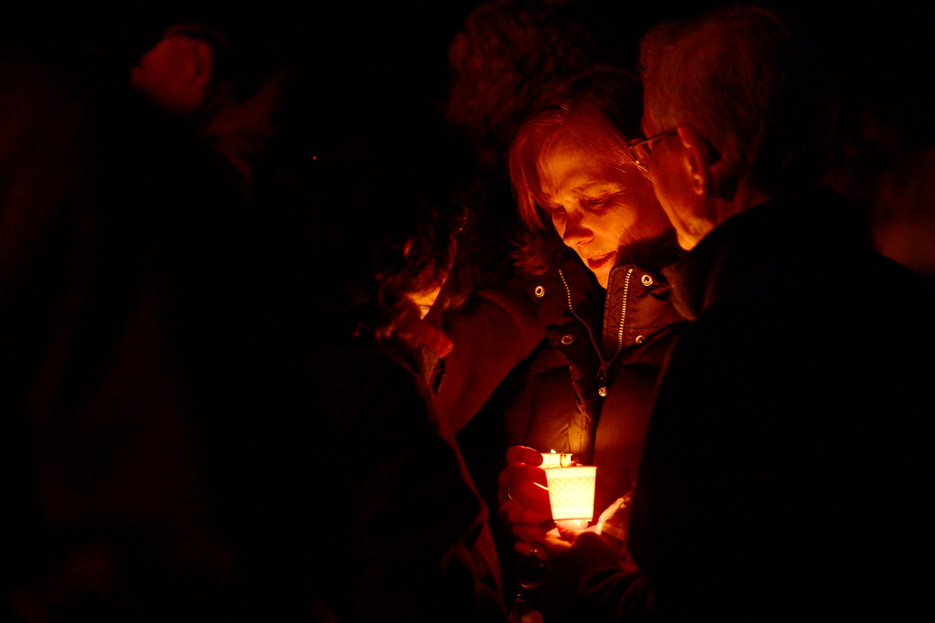 . A family member of Dr. Kenneth Atkinson is consoled by neighbors during a vigil for Dr. Kenneth Atkinson on April 5, 2016 in Centennial, Colorado. Close to 400 people showed up to pay their respects to Dr. Atkinson, who lost his life trying to protect a woman whose husband shot her. (Photo by Brent Lewis/The Denver Post)