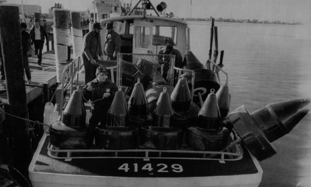 Description of . Coast Guard crewmen loaded date buoys Wednesday at the Coast Guard Station in Port Canaveral. The buoys were taken to the area of impact in the Atlantic Ocean where the debris from the Space Shuttle is believed to have fallen.   Denver Post Library Archive