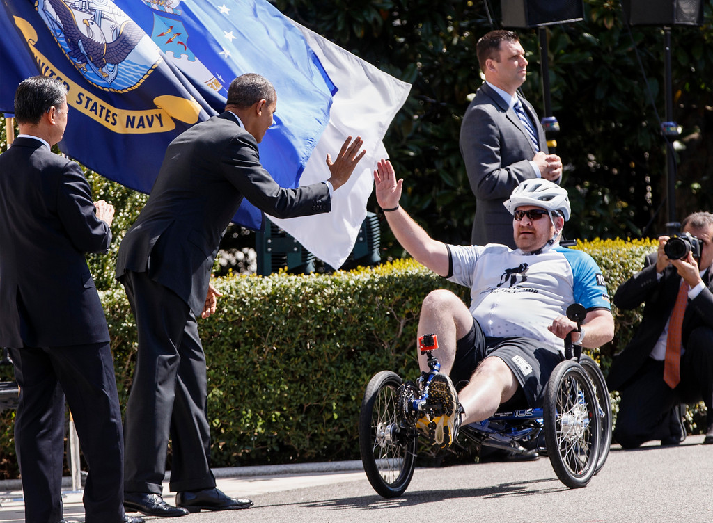 . President Barack Obama, accompanied by Veterans Affairs Secretary Eric Shinseki, left, welcome the Wounded Warrior Project�s Soldier Ride as they circle the South Lawn of the White House in Washington, Thursday, April 17, 2014. The cyclists were in specially built bikes that could accommodate amputations or other injuries. (AP Photo/J. Scott Applewhite)