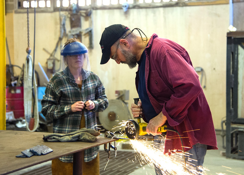 Professor Jack Gron demonstrates how to safely use a metal grinder during Advanced Sculpture.