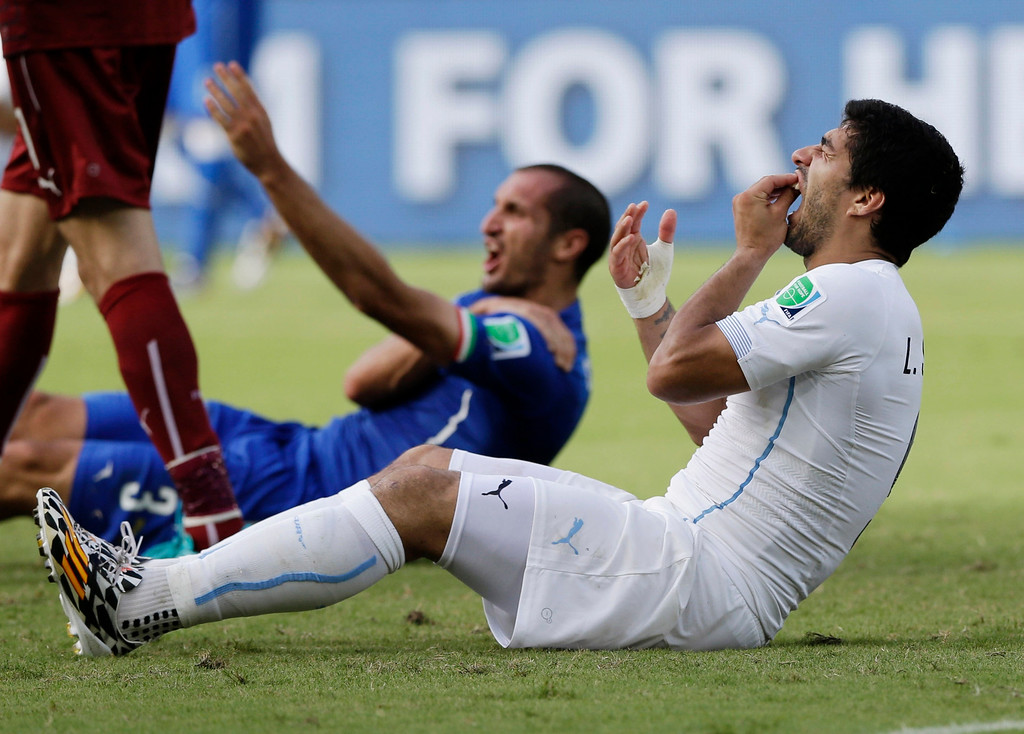 . Uruguay\'s Luis Suarez holds his teeth after running into Italy\'s Giorgio Chiellini\'s shoulder during the group D World Cup soccer match between Italy and Uruguay at the Arena das Dunas in Natal, Brazil, Tuesday, June 24, 2014. (AP Photo/Ricardo Mazalan, File)