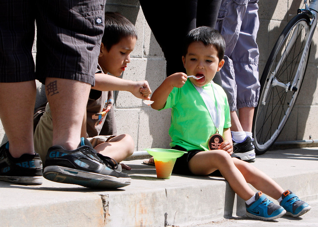 . Arthur Zavala, 3, enjoys shaved ice after placing third in his race at the Redlands Bicycle Classic on Saturday, April 5, 2014 in Redlands, Ca. (Photo by Micah Escamilla for the Redlands Daily Facts)