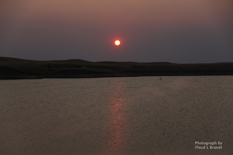 Havre Daily News/Floyd Brandt  Sunset on Beaver Creek Reservoir with a red tint from  thesmoke of all the fires in Montana Tuesday, Thank you to all the businesses that have donated to the Left Fork Fire effort, Havre Tire, Town Pump, Pizza Hut, the Farmers and Ranchers for the use of their water trucks.