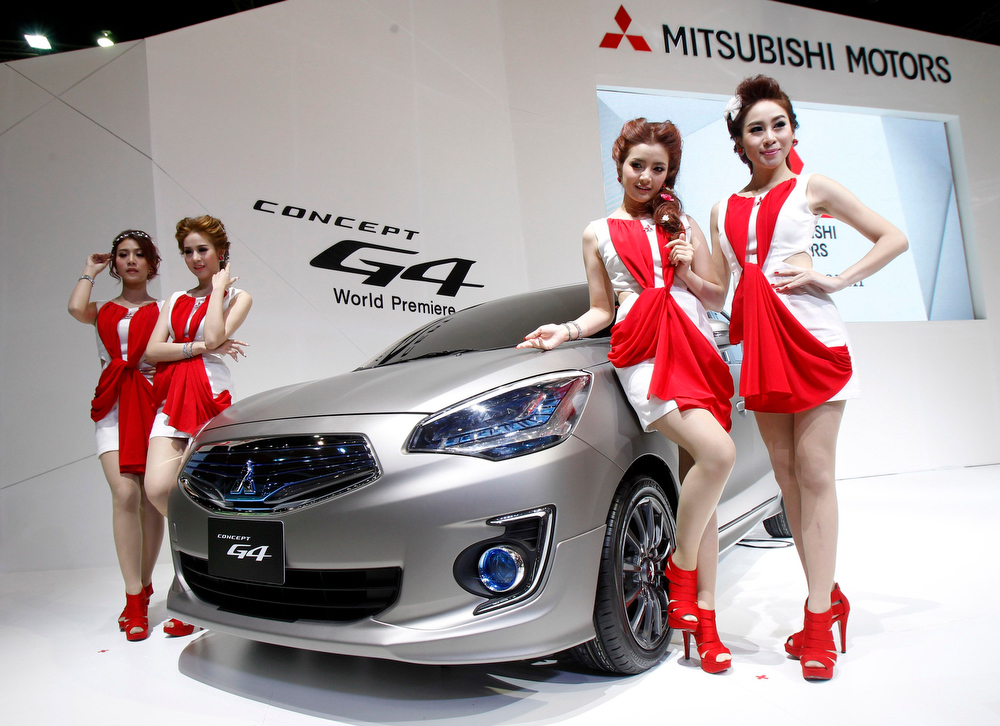 . Models pose beside a Mitsubishi G4 Concept car during a media presentation of the 34th Bangkok International Motor Show in Bangkok March 26, 2013. The Bangkok International Motor Show will be held from March 27 to April 7. REUTERS/Chaiwat Subprasom
