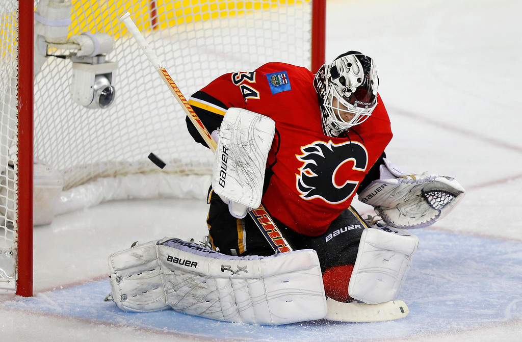 . The puck goes past Calgary Flames\' goalie Miikka Kiprusoff for a goal by Colorado Avalanche\' PA Parenteau (not seen) during the second period of their NHL hockey game in Calgary, Alberta, January 31, 2013. REUTERS/Todd Korol
