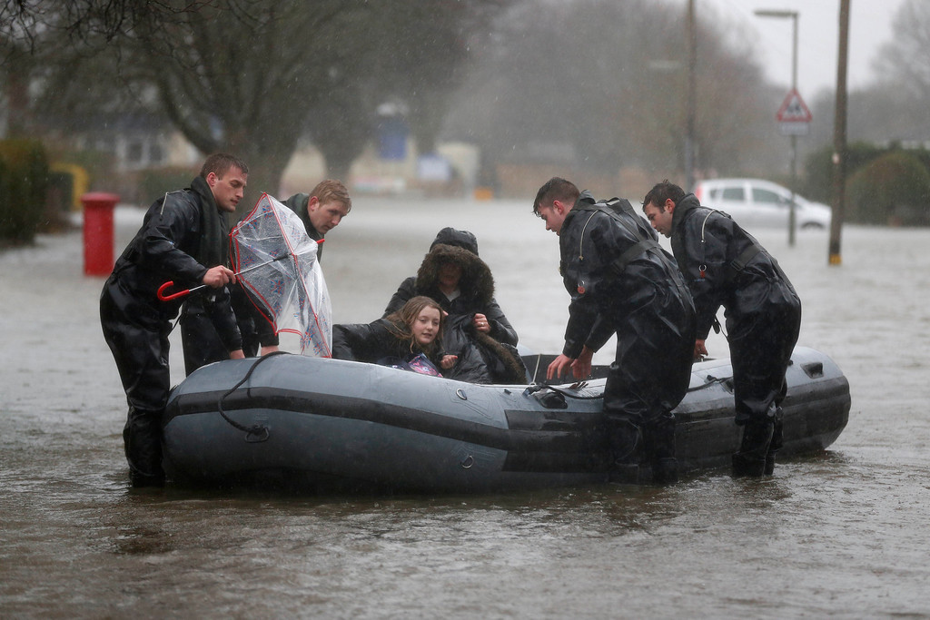 ". Soldiers from the Royal Engineer evacuate residents through a flooded road, in Egham, England, Wednesday, Feb. 12, 2014. Prime Minister David Cameron insisted Tuesday that money is no object in the battle against the widespread flooding that has engulfed parts of England. Canceling a visit to the Middle East to oversee flood-fighting efforts, he told journalists that ""whatever money is needed for this relief effort will be spent\"" as Britain deals with some of its wettest weather in 250 years.  (AP Photo/Sang Tan)"