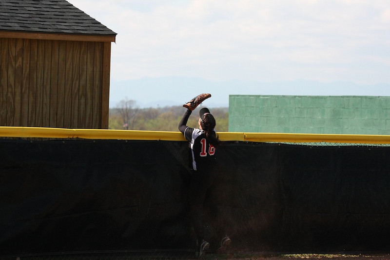 Number 18, Kelsey Witter, attempts to catch a fly ball over the fence.