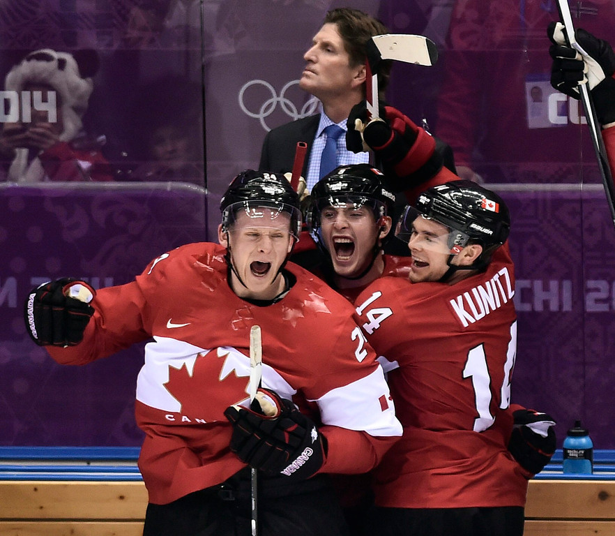 . Canada players Corey Perry, left, Matt Duchene, center, and Chris Kunitz, right celebrate on the bench as head coach Mike Babcock looks on after Canada beat the USA 1-0 in a men\'s semifinal ice hockey game at the 2014 Winter Olympics, Friday, Feb. 21, 2014, in Sochi, Russia. (AP Photo/The Canadian Press, Nathan Denette)