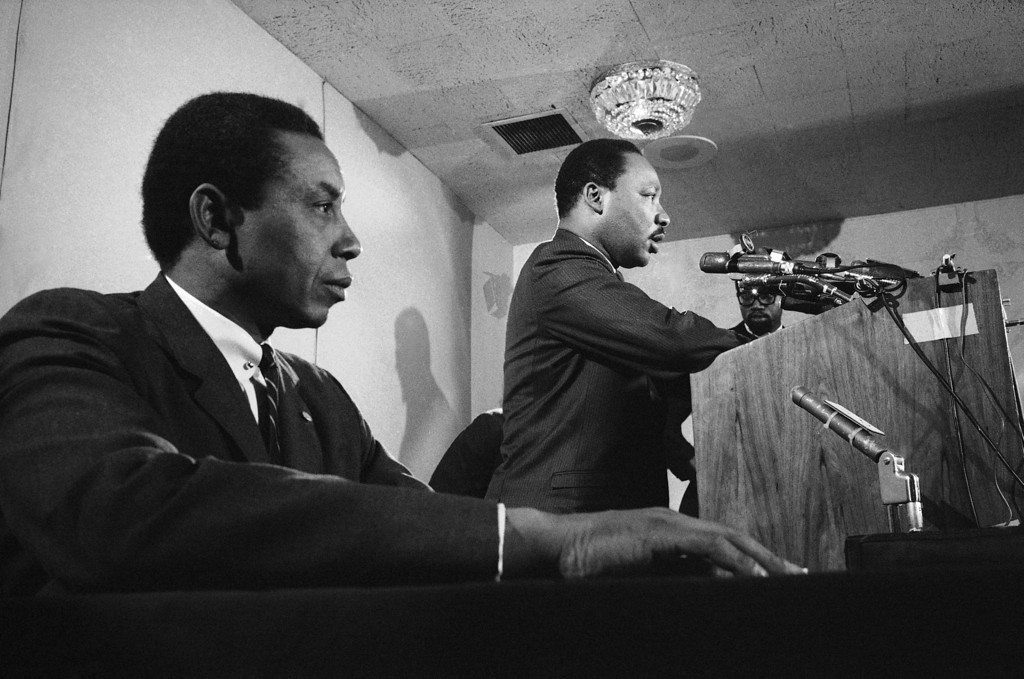 . Dr. Martin Luther King, head of the Southern Christian Leadership Conference, tells news conference that he and his organization support a boycott of the Olympic games by African American athletes in New York, Dec. 14, 1967. At left is Floyd McKissick, national director of the Congress of Racial Equality (CORE), who also announced support for the boycott. (AP Photo/Eddie Adams)