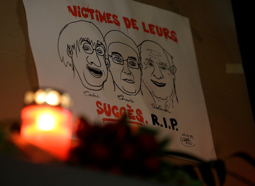 ". A drawing depicting cartoonist Jean Cabut, left, Charlie Hebdo editor Stephane Charbonnier, center, and cartoonist Georges Wolinski, all three of whom were killed when masked gunmen stormed the Paris offices of a weekly newspaper Charlie Hebdo and reading in French, ""Victims of their success, R.I.P\"", is placed outside the French Embassy as people gather to express solidarity with victims of the attack in Berlin, Germany, Wednesday, Jan. 7, 2015. Three masked gunmen shouting \""Allahu akbar!\"" stormed the Paris offices of a satirical newspaper Wednesday, killing 12 people, including its editor, before escaping in a car. It was France\'s deadliest postwar terrorist attack. (AP Photo/Michael Sohn)"
