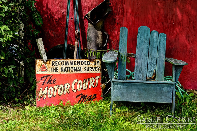 An old sign sitting next to a broken chair.