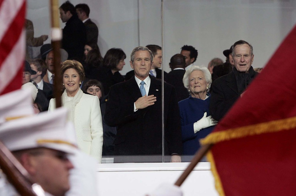 . President George W. Bush is flanked by first lady Laura Bush, left, his father, former President George H. W. Bush and his wife, former first lady Barbara Bush, right, as they watch the Inaugural Parade Thursday, Jan. 20, 2005, in Washington. (AP Photo/Elise Amandola)