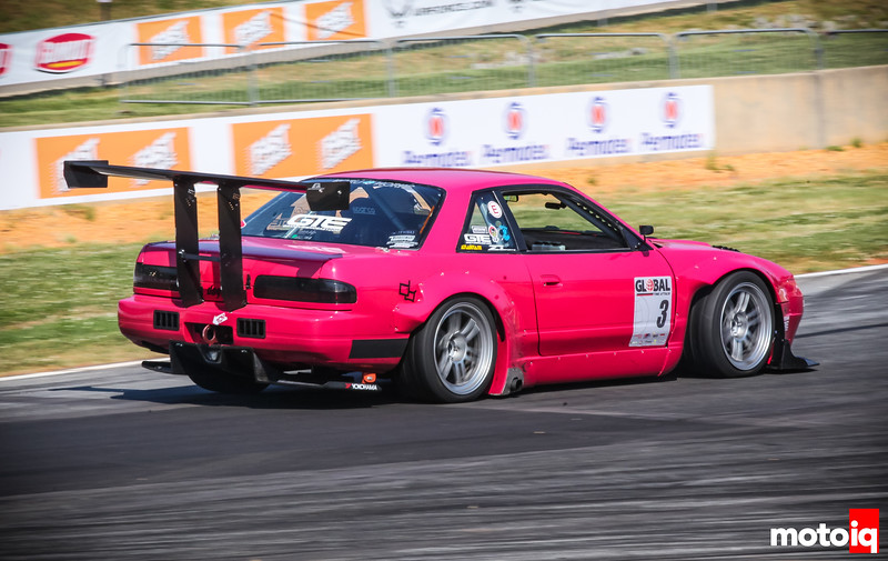 Pink S13 cornering hard driving away and to right of frame