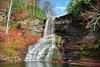 Beautiful tall waterfall falling into a lagoon during autumn.