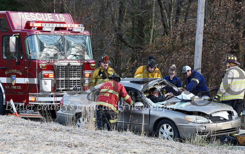 Harold Aughton/Butler Eagle: Saxonburg paramedics tend to a man who became trapped in his car after a tree fell on his car while driving on Dinnerbell Road, Wed. Nov. 27, 2019.