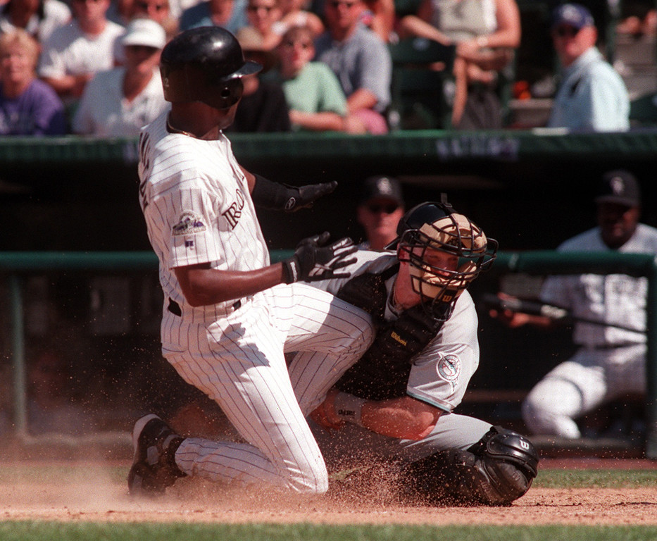. Marlins Greg Zaun brock the sliding of Rockies Darryl Hamilton in the 5 inning on Monday.