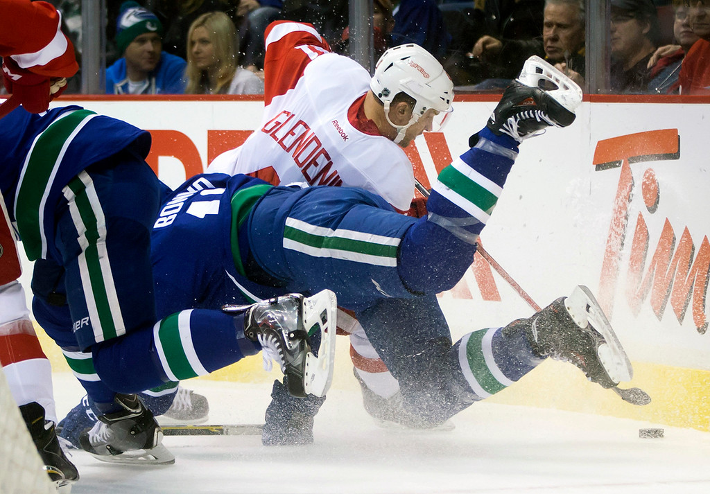 . Vancouver Canucks\' Nick Bonino, left, and Detroit Red Wings\' Luke Glendening collide during the first period of an NHL hockey game in Vancouver, British Columbia on Saturday, Jan. 3, 2015. (AP Photo/The Canadian Press, Darryl Dyck)