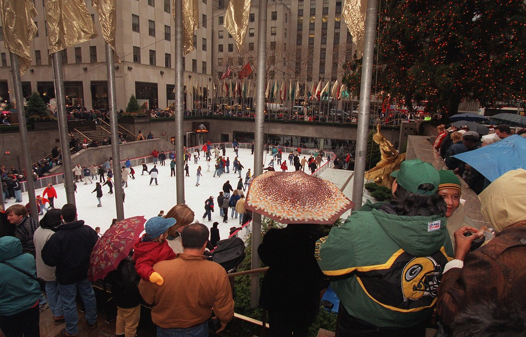 . A light rain can\'t keep tourists and sightseers from ringing the skating rink at Rockefeller Center near the famed Christmas tree Friday, Dec. 12, 1997, in New York. Nearby Radio City Music Hall is reporting record sales for its entertainment and local officials are saying it is the one of the busiest and most crowded Christmas seasons ever. (AP Photo/Ed Bailey)
