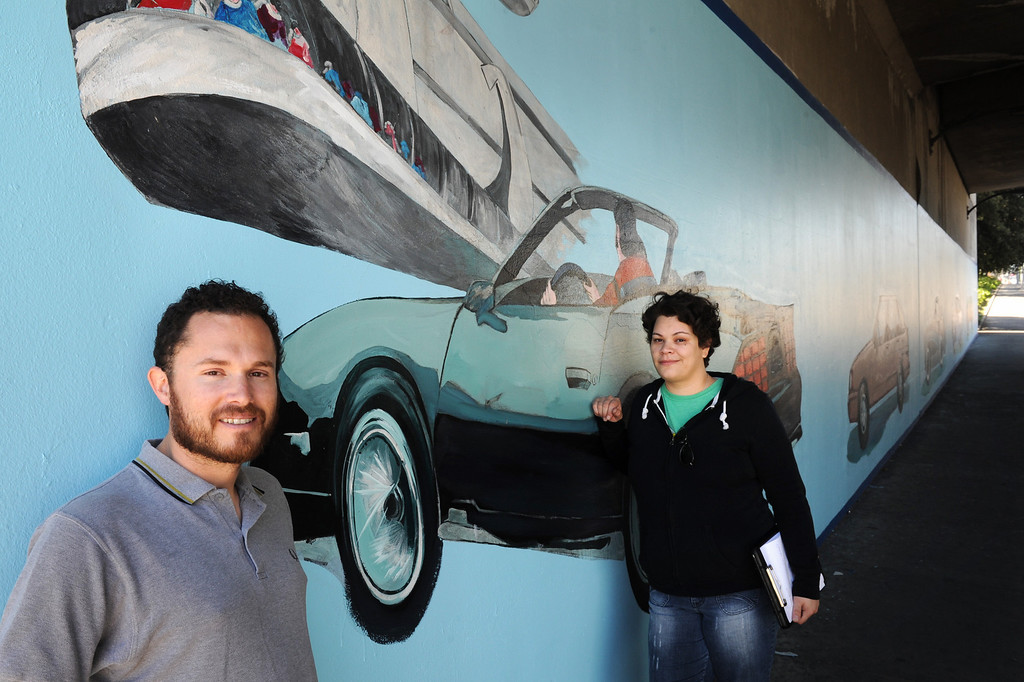 """. Elijah Flores, left, and Erika Tachet, are making a documentary film of their grandfather, muralist Alfredo Diaz Flores, and the restoration of his mural \""""Panorama: G.M. Recollections from the Past,\"""" on Van Nuys Boulevard in Panorama City. (Michael Owen Baker/Staff Photographer)"""