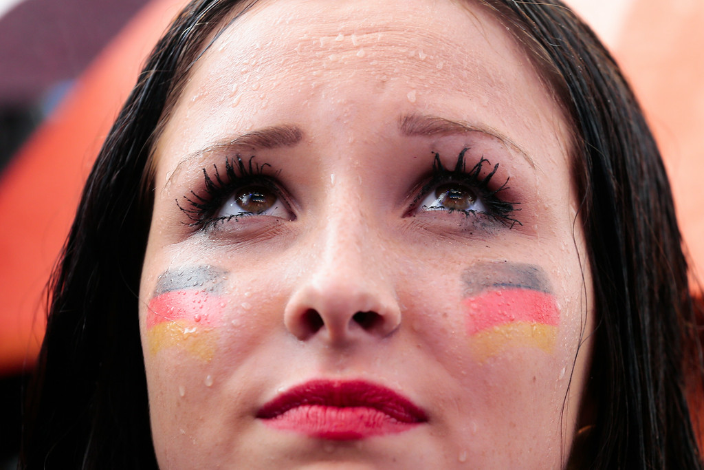 . Rain falls on the face of a woman, as she watches the World Cup 2014 soccer match between Germany and United States, at a public viewing named \'Fan Mile\' in Berlin, Thursday, June 26, 2014.  (AP Photo/Markus Schreiber)