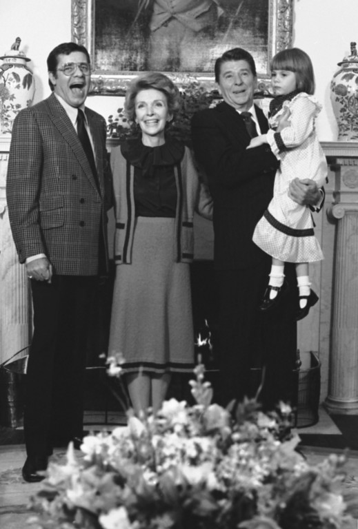 . Jerry Lewis, left, national chairman of the Multiple Sclerosis Fund, left, clowns with Pres. Ronald Reagan, right, and Mrs. Nancy Reagan, as the President holds the national poster child Christi Barlett in the Oval Office, Monday, March 16, 1981, Washington, D.C.  (AP Photo/Charles Tasnadi)