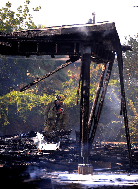 . A firefighter looks at a vacant home that was destroyed by a four-alarm fire along the 700 block of Seventh Street in San Bernardino August 18, 2013. GABRIEL LUIS ACOSTA/STAFF PHOTOGRAPHER.