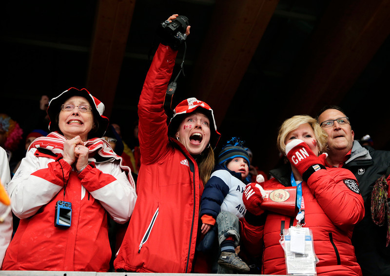 . Supporters of Canada CAN-1, Kaillie Humphries and Heather Moyse, cheer at the finish area during the women\'s bobsled competition at the 2014 Winter Olympics, Wednesday, Feb. 19, 2014, in Krasnaya Polyana, Russia. (AP Photo/Jae C. Hong)