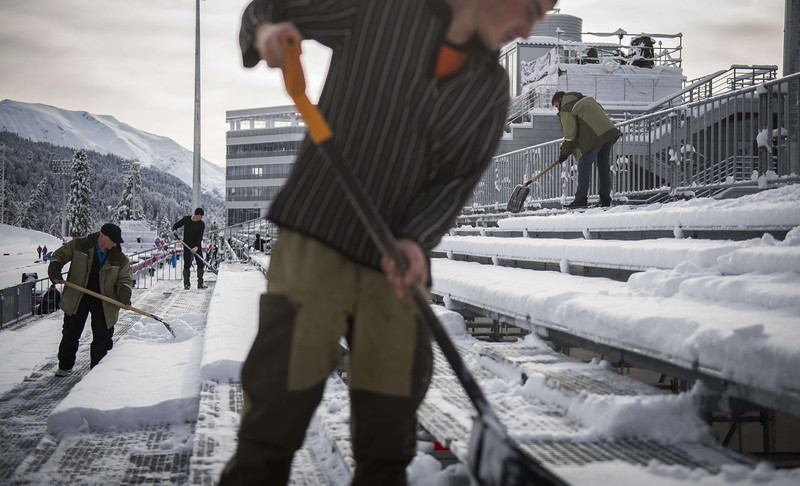 . Workers use shovels to clear snow off the spectators stands in the Biathlon finish area at the Laura Cross Country and Biathlon Center in Rosa Khutor on February 19, 2014 before the Women\'s Cross-Country Skiing Team Sprint Classic Semifinals during the Sochi Winter Olympics, as 20 cm of snow had fallen overnight. (ODD ANDERSEN/AFP/Getty Images)