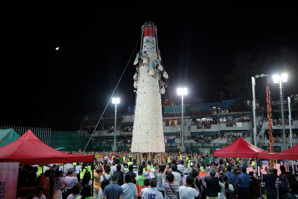 . Participants climb up the bun tower during the bun snatching competition on the outlying Cheung Chau island in Hong Kong, Wednesday, May 23, 2018,  to celebrate the Bun Festival. During the Bun Festival, the Taoist God of the Sea, is worshipped and evil spirits are scared away by loud gongs and drums during the procession. The celebration includes bun scrambling, parades, opera performances, and children dressed in colorful costumes. (AP Photo/Kin Cheung)