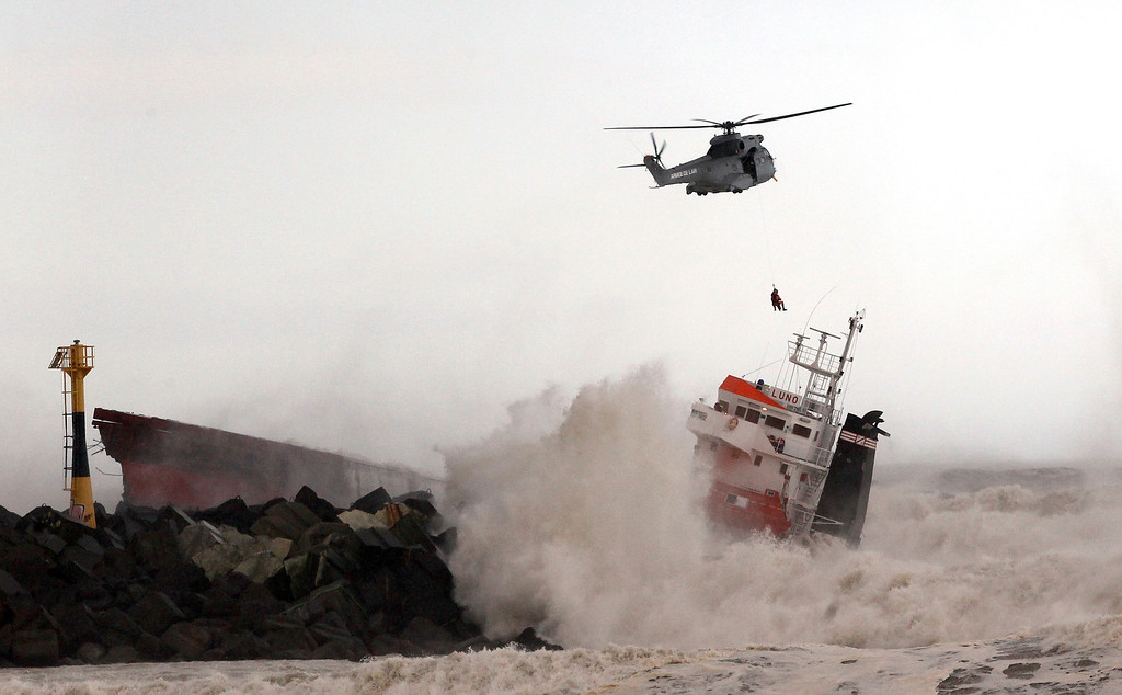. A helicopter lowers a rescue worker toward a Spanish cargo ship that slammed into a jetty in choppy Atlantic Ocean waters off Anglet, southwestern France, Wednesday Feb. 5, 2014.  (AP Photo/Bob Edme)