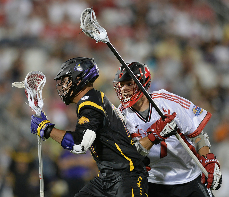 . COMMERCE CITY, CO - JULY 17: Iroquois midfielder Jeff Shattler (77) made a run past Canada defender Dan Coates (7) in the second half. The Iroquois Nationals took on Canada in a FIL World Championship semifinal game Thursday night, July 17, 2014.  Photo by Karl Gehring/The Denver Post