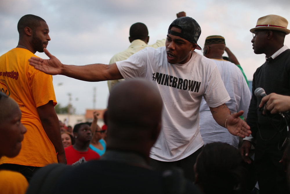 . Rapper Nelly joins demonstrators protesting the shooting death of Michael Brown as they make their voices heard on August 18, 2014 in Ferguson, Missouri. Protesters have been vocal asking for justice in the shooting death of Michael Brown by a Ferguson police officer on August 9th.  (Photo by Joe Raedle/Getty Images)