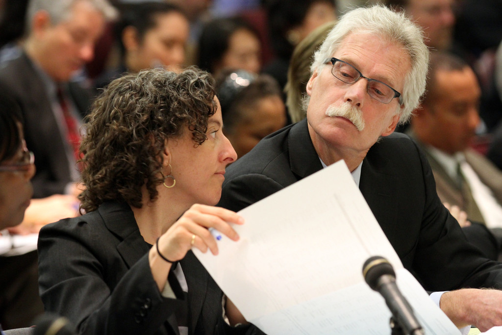 . Kate Hallward, counsel for ATU 1555, and Vincent Harrington, counsel for SEIU, look over some documents as BART management presents its side of the negotiations before a state panel commissioned by Gov. Jerry Brown at the Elihu M. Harris State Building in Oakland, Calif., on Wednesday, Aug. 7, 2013. (Laura A. Oda/Bay Area News Group)