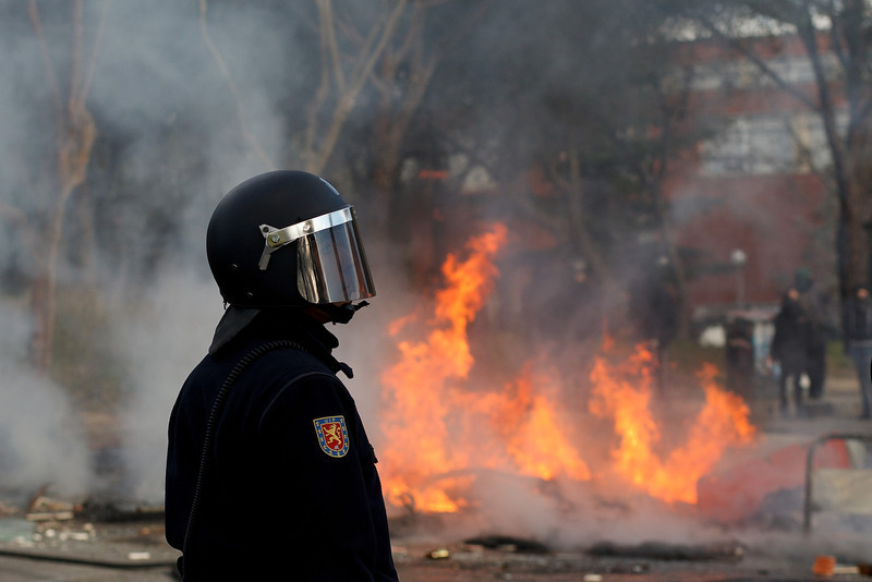. A riot policeman stands near a burning barricade during a protest against the government\'s education reforms and cutbacks in university grants and staffing in Campus Ciudad Universitaria on March 26, 2014 in Madrid, Spain. The students began occupying a campus building at Ciudad Universitaria several days ago in protest against the governments\' cuts. Today, they were removed from the premises by police, who made fifty arrests, after the University requested their assistance.  (Photo by Pablo Blazquez Dominguez/Getty Images)