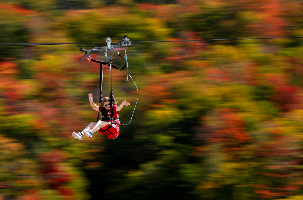 . Katie McWalter of Southborough, Mass., sails by the fall foliage while riding the ZipRider at Wildcat Mountain, Saturday, Sept. 23, 2017, in Pinkham Notch, N.H. The first weekend of autumn is unusually warm with temperatures climbing into the upper 80s. (AP Photo/Robert F. Bukaty)