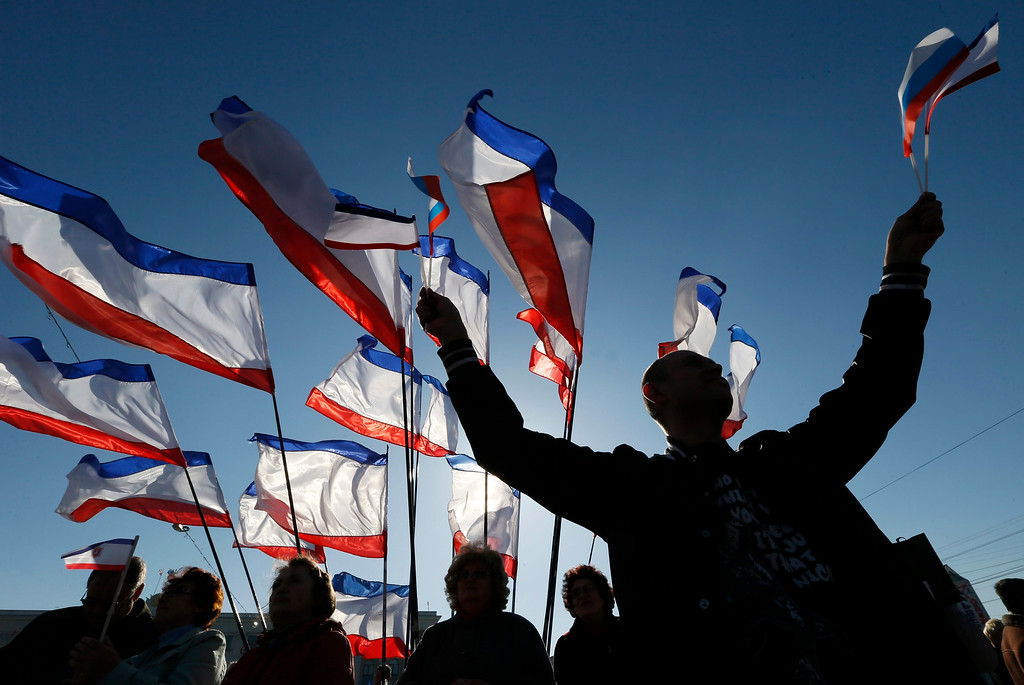 . A man holds Russian and  Crimean flags during a rally in front of Crimean flags at Lenin Square in Simferopol, Crimea, Ukraine, 15 March 2014. The Moscow-leaning Crimea region is due to hold a referendum on 16 March on whether to break away from Ukraine and join Russia, with observers fearing worsening violence on the peninsula ahead of the vote. Hopes for a diplomatic solution to the crisis faded on 14 March after six-hour talks between US Secretary of State John Kerry and his Russian counterpart Sergei Lavrov ended with \'no common vision\', as Lavrov put it.  EPA/YURI KOCHETKOV