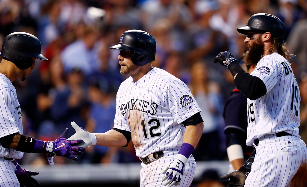 . Colorado Rockies\' Mark Reynolds, center, is congratulated by Carlos Gonzalez, left, and Charlie Blackmon as Reynolds crosses home plate after hitting a three-run home run off Cleveland Indians relief pitcher Zach McAllister in the fifth inning of an interleague baseball game Tuesday, June 6, 2017, in Denver. The Rockies won 11-3. (AP Photo/David Zalubowski)