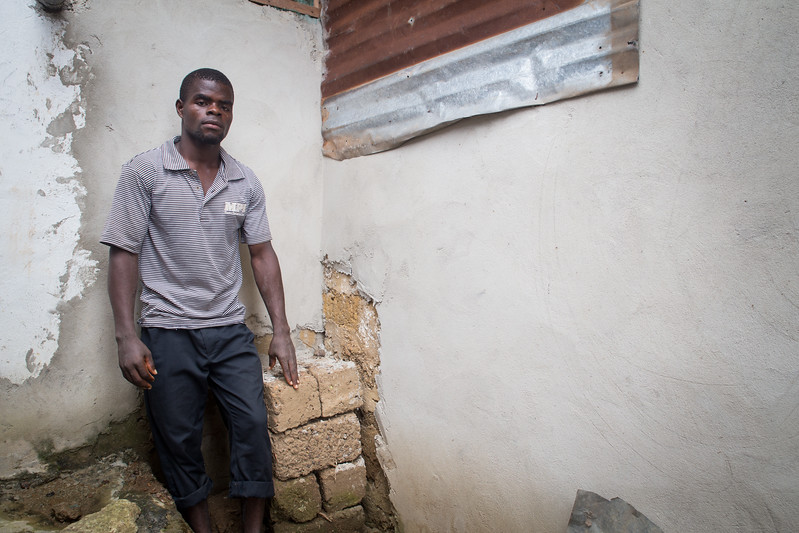 Monrovia, Liberia October 8, 2017 - Boimah Dorley stands next to some of the bricks he makes to earn a living.