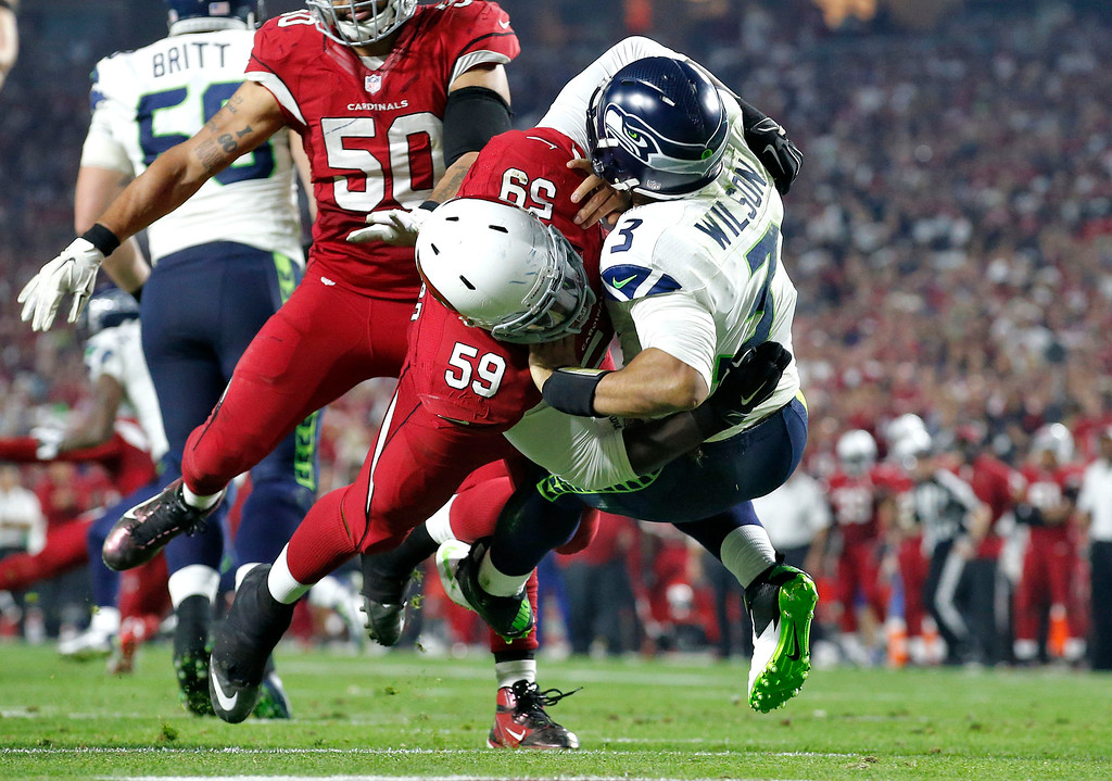 . Seattle Seahawks quarterback Russell Wilson (3) is hit by Arizona Cardinals linebacker Marcus Benard (59) during the second half of an NFL football game, Sunday, Dec. 21, 2014, in Glendale, Ariz. (AP Photo/Ross D. Franklin)