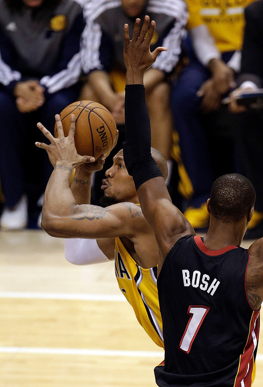 . Indiana Pacers forward David West, left, shoots around Miami Heat center Chris Bosh (1) during the first half of Game 2 of the NBA basketball Eastern Conference finals in Indianapolis, Tuesday, May 20, 2014. (AP Photo/AJ Mast)