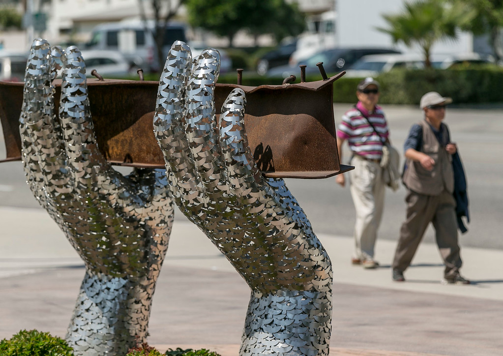 ". In this Friday, Aug. 26, 2016 photo, pedestrians walk by artist Heath Satow\'s sculpture ""Reflect,\"" made with a damaged, rusted I-beam from the collapsed World Trade Center buildings, outside the Rosemead, Calif., city hall plaza. The 9/11 memorial sculpture has 2,976 interlocking birds representing individual victims from the 2001 attacks. (AP Photo/Damian Dovarganes)"