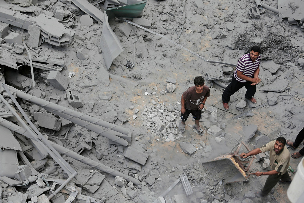 . Palestinians from a neighboring apartment building carry out debris as they walk on the rubble of the offices of the Hamas movement\'s Al-Aqsa satellite TV station, in Gaza City, northern Gaza Strip, destroyed by an Israeli strike, Tuesday, July 29, 2014. Early Tuesday, Israel warplanes struck a series of targets in Gaza City, including the top Hamas leader in Gaza, Ismail Haniyeh\'s house and government offices, while Gaza\'s border area with Israel was hit by heavy tank shelling. (AP Photo/Lefteris Pitarakis)