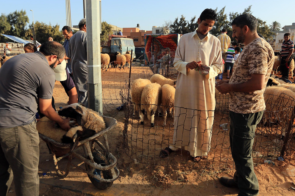 . Libyan men buy a sheep at a livestock market in the capital Tripoli October 3, 2014, on the eve of the Muslim holiday of Eid al-Adha or Feast of the Sacrifice, which marks the end of the annual pilgrimage to Mecca and is celebrated in remembrance of Abraham\'s readiness to sacrifice his son to God. MAHMUD TURKIA/AFP/Getty Images