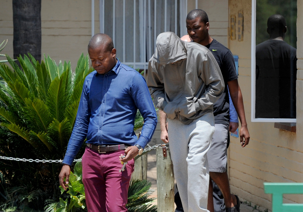 Description of . South Africa's Olympic sprinter Oscar Pistorius (C) leaves the Boshkop police station on February 14, 2013 in Pretoria East, to be taken into police custody after allegedly shooting dead his model girlfriend having mistaken her for an intruder at his upscale home.   AFP PHOTO-/AFP/Getty Images