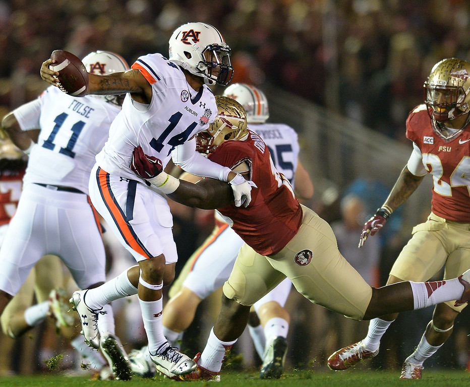 . Auburn QB Nick Marshall tries to avoid Florida State\'s Mario Edwards Jr. in the first quarter of the BCS national championship game at the Rose Bowl, Monday, January 6, 2014. (Photo by Michael Owen Baker/L.A. Daily News)