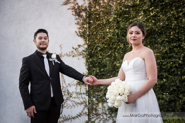 bride and groom holding hands at Mt Hamilton GrandView Restaurant in San Jose