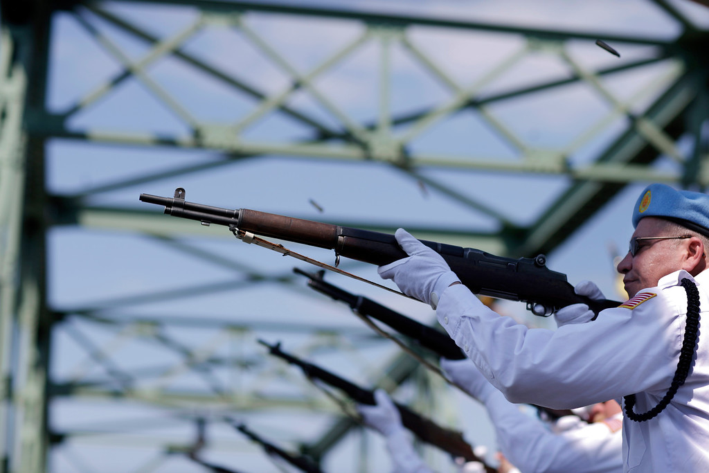 . An Honor Guard fires a 21-gun salute as they stand on the Uhlerstown-Frenchtown Bridge over the Delaware River, between Uhlerstown, Pa. and Frenchtown, N.J., during Memorial Day ceremonies Monday, May 25, 2015, in Frenchtown, N.J. (AP Photo/Mel Evans)