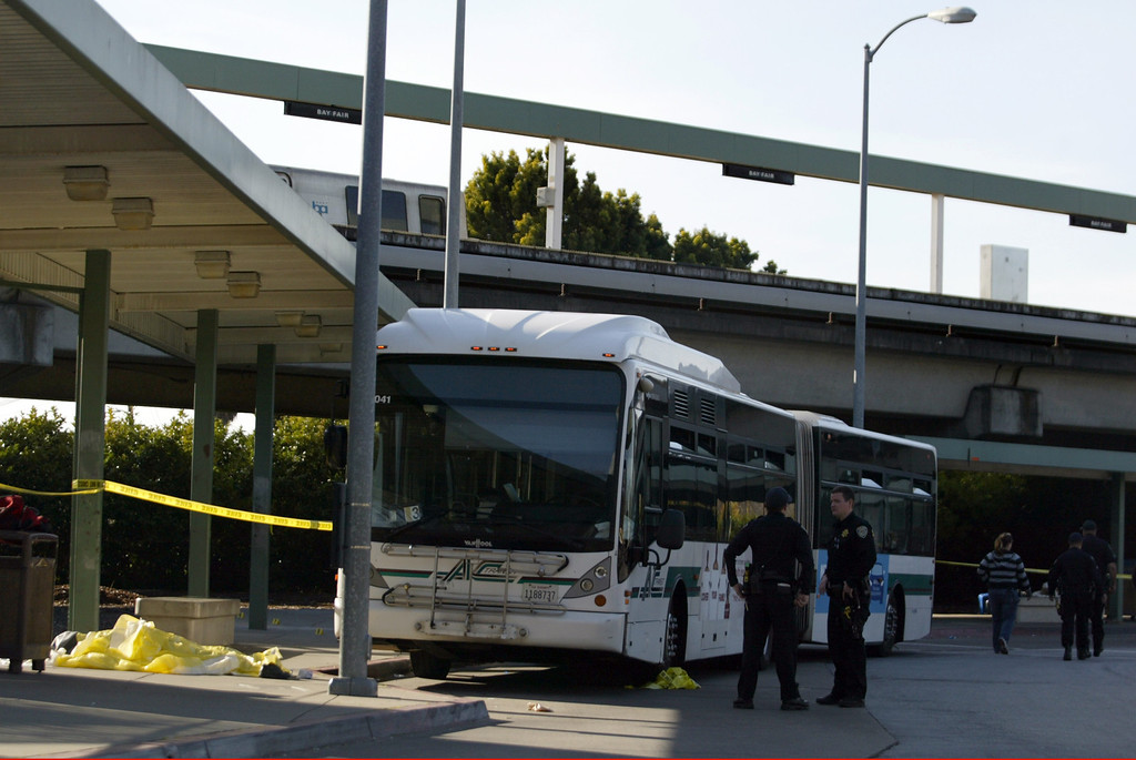 . A dead body, left, lies on the sidewalk next to an AC Transit bus as police investigate the fatal shooting in the bus yard outside the Bay Fair BART station in San Leandro, Calif., on Saturday, Jan. 19, 2013. (Ray Chavez/Staff)