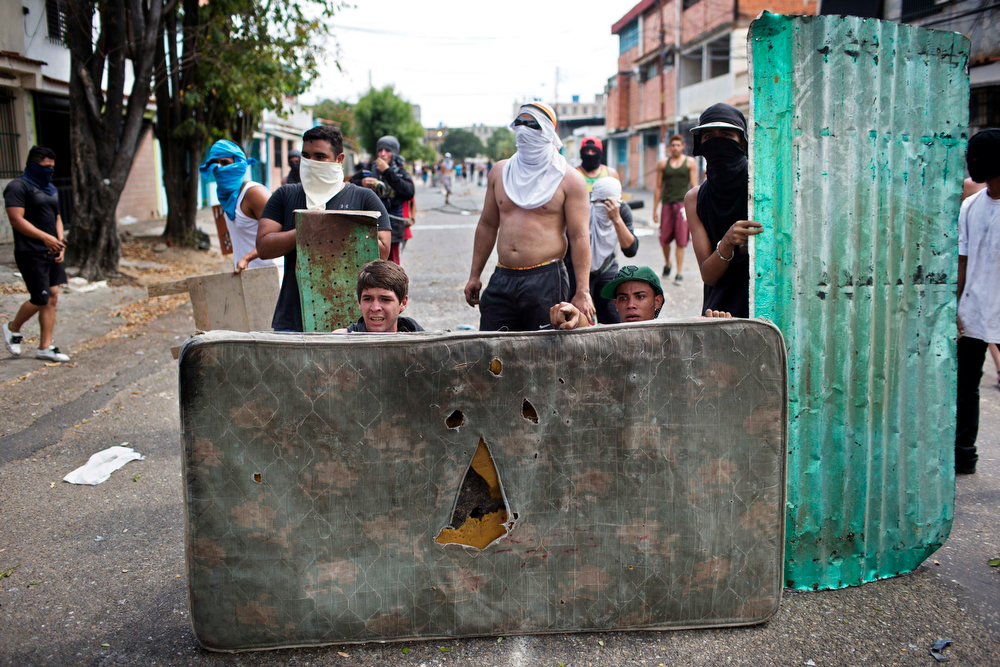 . Demonstrators use a mattress and sheet metal to shield themselves during clashes with police during an anti-government protest in Valencia, Venezuela, Wednesday, Feb. 26, 2014. The protests began with students and were soon joined by others in several cities, upset over crime, economic problems and heavy-handed government response to the protests. (AP Photo/Rodrigo Abd)