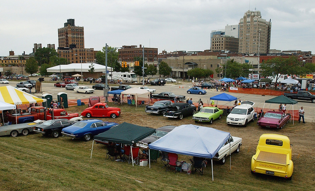 . Parked classic cars, that are with the Flaming Pistons car club, are parked on the west side of Woodward, as they watch other motorists make their way along southbound Woodward, during the Dream Cruise.  Photo taken on Saturday, August 21, 2010, in Pontiac, Mich.  (The Oakland Press/Jose Juarez)